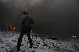 Protester walking through Grushevskogo str. covered with smoke of the fire set by the protesters to prevent internal forces from crossing the barricade line. Kyiv, Ukraine. Jan 22, 2014.jpg
