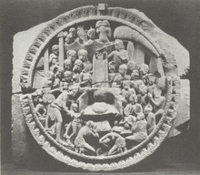 Stone relief with throne at the center and numerous figures surrounding the throne, including a mother and her child