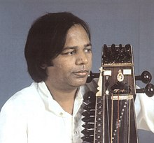 A middle-aged man wears a shirt and looks to the side with a bowed instrument held close to his body.