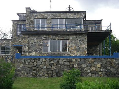 photograph of a stone-built house in 'International' style, with blue woodwork