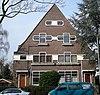 foto van Vrijstaand dubbel woonhuis met ondiepe voortuin achter een ligusterhaag in karakteristieke Engelse Landhuisstijl
