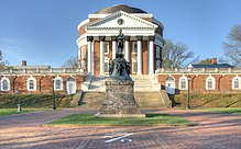 A green statue on a brown pedestal in front of a red brick, Neoclassical dome with a large portico on the front and covered walkway on the sides.