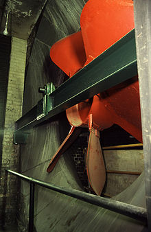 Large red six-bladed fan, fitted to a steel girder, enclosed inside a concrete and brick funnel.