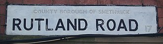 "Smethwick - Street nameplate on Rutland Road, Smethwick in April 2007, showing painted out ""County Borough"" lettering, and the original B17 district code"