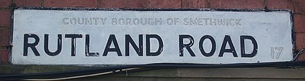 "Street nameplate on Rutland Road, Smethwick in April 2007, showing painted out ""County Borough"" lettering, and the former B17 district code RutlandRoadSignSmethwick.jpg"