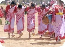 Barefoot women in pink saris dancing