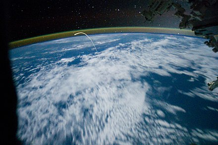 Glowing plasma trail from Space Shuttle Atlantis re-entry as seen from the Space Station Space Shuttle Atlantis in the sky on July 21, 2011, to its final landing.jpg