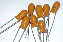 Solid-body, resin-dipped 10 μF 35 V tantalum capacitors. The + sign indicates the positive lead.