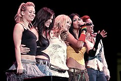 Five young women smiling and standing close together, one of whom (lead singer Nicole Scherzinger) is singing into a microphone with her left arm outstretched.