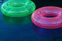Translucent green and pink swim rings on water 2645435443.jpg