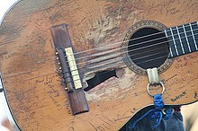 A classical guitar. There are several damages in the soundboard, near the sound hole there is a big hole and the wood is worn out in the surrounding areas of it, the guitar has several signatures on it. there is a blue and white strap in the soundhole.