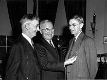 three men in suits. The one on the right is wearing a medal.