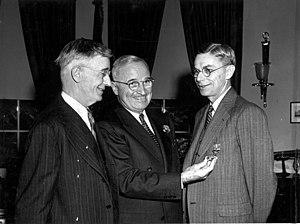 Drei lächelnde Männer in Anzügen
