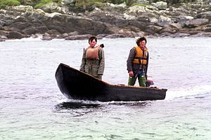 Currach - Fishermen in currach with outboard motor heading back to their harbour at the westcoast of Ireland in 1986