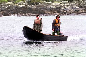 Currach - Fishermen in currach with outboard motor heading back to their harbour at the west coast of Ireland in 1986