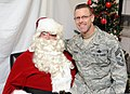 U.S. Air Force Chief Master Sgt. Bryan Creager, the command chief master sergeant of the 97th Air Mobility Wing, sits with Santa Claus during an open house at the Airman and Family Readiness Center at Altus Air 131212-F-FV476-004.jpg
