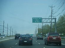 A six lane divided highway lined with power lines. A green sign over the road reads Scudders Mill Road ¼ mile.