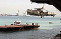 "US Navy 030220-N-1356A-013 An E-2C ""Hawkeye"" is hoisted and lowered onto a barge in Bahrain.jpg"