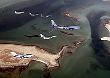 Photo of seven modern aircraft of differing designs flying in formation above a group of sandy islands