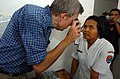 US Navy 050325-N-8629M-220 James Honl, a medical professional from the Military Sealift Command (MSC) hospital ship USNS Mercy (T-AH 19), conducts an eye examination for an Indonesian woman.jpg