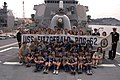 US Navy 061015-N-5334H-179 USS Fitzgerald (DDG 62) Commanding Officer, Cmdr. David Hughes and Executive Officer, Lt. Cmdr. John Tolg hold up the ship's banner with children and adults from the Cub Scouts Tokyo Group.jpg
