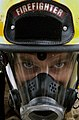 US Navy 071107-N-3750S-022 Special Operations Master Chief (SEAL) Victor Licause dons a San Antonio firefighter's headgear and full body gear in order to perform a sequence of timed drills.jpg