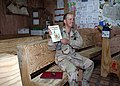 US Navy 071213-N-6748R-074 Lt. Jon Hilton, assigned to Naval Mobile Construction Battalion (NMCB) 15, shows the book Tales of Peter Rabbit and Friends for his children during a United Through Reading (UTR) recording session.jpg