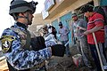 US Navy 081206-N-1810F-259 An Iraqi National Policeman hands out leaflets to Iraqi civilians during a walking patrol through the Rashid community in Bahgdad.jpg