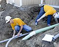US Navy 100512-N-0869H-054 Navy Counselor 1st Class Chris Oliveria and Hospital Corpsman 1st Class Devin McConnell measure pipe for conduit during a Habitat for Humanity building project.jpg