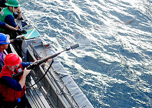 US Navy 120119-N-ZF681-083 Gunner's Mate 2nd Class Erik Trudel, assigned to the guided-missile destroyer USS Halsey (DDG 97), fires a shot line.jpg