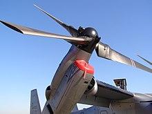 Un gros plan du rotor et du moteur d'un MV-22B légèrement incliné vers le haut.