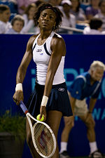 A black woman is serving the ball, and is wearing a white sleeveless top and blue skirt
