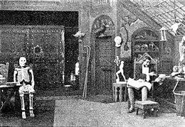 Victor Frankenstein, sidigita en lia laboratorio, gestadante direkte al kranio tenita en lia alia mano