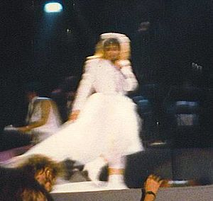 """The Virgin Tour - Madonna wearing a wedding dress, while performing """"Like a Virgin"""" during the show."""