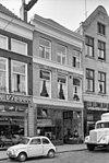 foto van Pand met jongere winkelpui in gepleisterde lijstgevel met vroeg neogotisch fries
