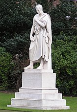 White stone statue of a man in a toga, in a park