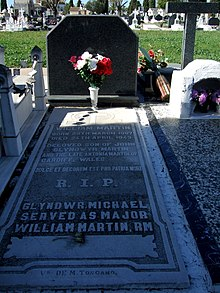 A large black marble memorial slab with flowers