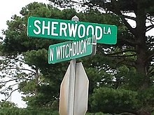 Sign reading 'Sherwood La' in one direction and N Witchduck Rd' in the other, in white lettering on a green background