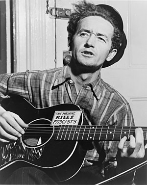 A black-and-white photograph taken indoors of Woody Guthrie wearing pinstripe trousers, a tartan shirt with top button undone, and a cap. He sits playing a six-string acoustic guitar, which is supported on one knee, and he appears to be singing. 'This Machine Kills Fascists' is written in all capital letters on a rectangular sticker, which is fixed onto the guitar.