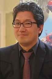 Yuji Naka, ein Japaner in Brille, schwarzem Anzug und roter Krawatte, im Jahr 2015. Er ist Mitschöpfer von Sonic the Hedgehog und Produzent von Sonic Heroes.