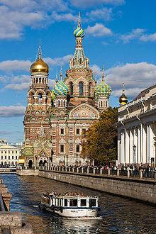 """""""Photographie de la cathédrale le long du canal Griboïedov. Un bateau-mouche passe au premier plan."""""""