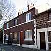 A row of brick cottages in two storeys with stone dressings and a prominent string course