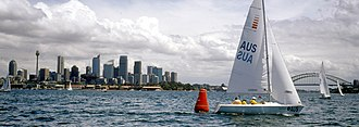 Sailing at the 2000 Summer Paralympics - Panoramic view of the paralympic sailing venue, Sydney Harbour, during competition at the 2000 Summer Paralympics. Members of the Australian Paralympic Sailing team with their boat can be seen in the foreground. The Sydney Harbour Bridge, Sydney Tower and the CBD can be seen in the background.
