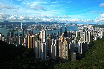 A panorama looking down on a city of skyscrapers. A land mass is seen in the distance, separated from the photographer's vantage point by a body of water.