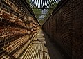 300 meter walk on a bare earth floor through narrow walkway, relieved by interesting pattern of light and shadowson the enclosing bare brick walls through a steel lattice roof - Ali Mardan Khan's Tomb and Gateway.jpg