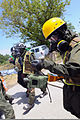 A U.S. Marine, right, with the Chemical Biological Incident Response Force, 2nd Marine Expeditionary Unit scans for the presence of radiation and other threats during a search and extraction mission at 120727-A-ZZ999-019.jpg