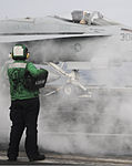 A U.S. Navy aviation boatswain's mate (equipment) holds a weight board as an F-A-18C Hornet aircraft assigned to Strike Fighter Squadron (VFA) 146 prepares to launch from the aircraft carrier USS Nimitz 130821-N-GA424-142.jpg