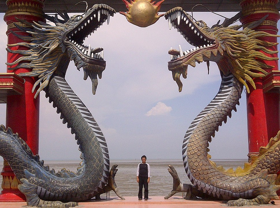 A visitor of Sanggar Agung Temple toke a picture under the dragon statues, Surabaya-Indonesia
