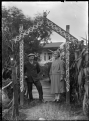 Albert Percy Godber and his wife Laura Godber standing under an archway decorated in Maori style in their garden at Silverstream ATLIB 311719.png