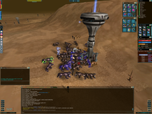Characters grouped around one of several man-made metal towers in a desert. A heads-up display with buttons, boxes containing text, and other objects line the periphery of the image.